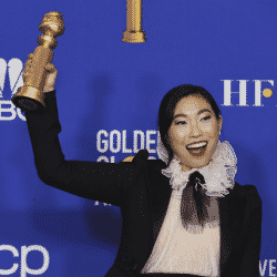 Awkwafina holds up her Golden Globe smiling at this year's event in Beverly Hills