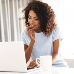 Pensive african woman using laptop computer while sitting at home with cup of coffee